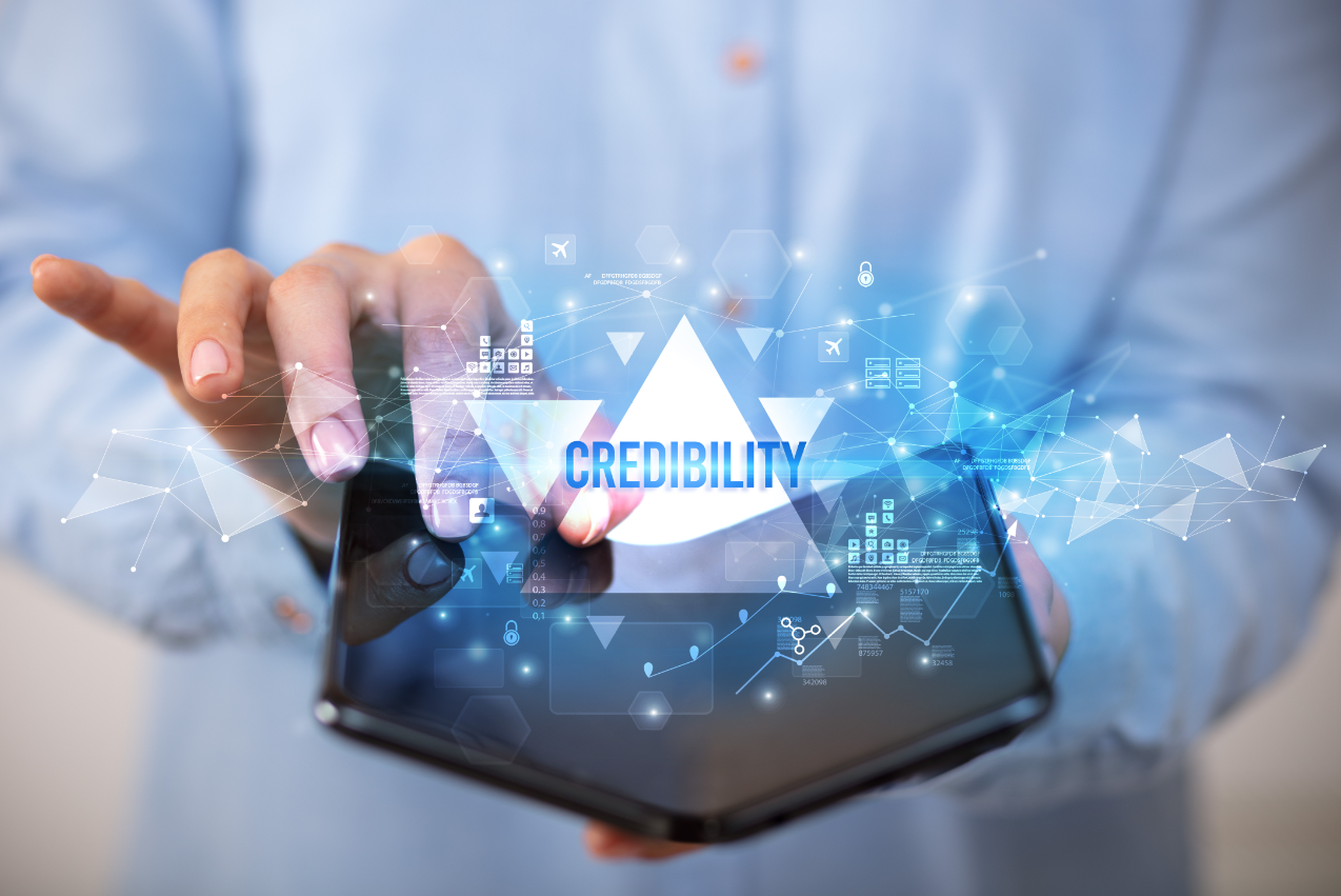 a woman holding a tablet with a credibility graphic